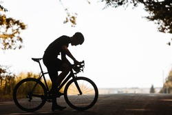 Silhouette of tired mature man in activewear taking rest during regular training outdoors. Side view of sportsman in helmet doing cycling on nature.