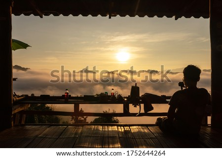 Silhouette of tourist on wooden terrace of noodle shop during a beautiful early morning sky with waves of fog at Baan Ja Bo village viewpoint of Pang Mapha, Mae Hong Son, Northern Thailand. Stockfoto ©
