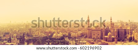 Silhouette of traditional arabic city with minarets and modern skyscrapers on a horizon. Mosque of Al Rifai and Madrasa of Sultan Hassan. Panoramic view of Cairo with landmarks of muslim architecture. #602196902