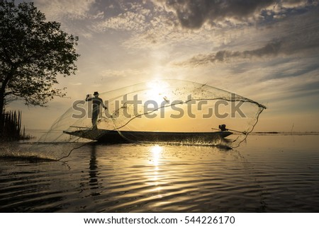 Silhouette of traditional fishermen throwing net fishing at sunrise time, livelihoods of fishermen at Pakpra, Phattalung in Thailand #544226170