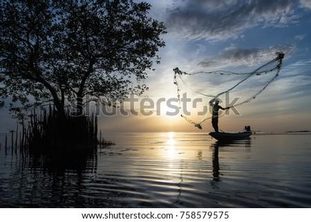 Silhouette of traditional fishermen throwing net fishing at sunrise time, livelihoods of fishermen at Pakpra, Phatthalung in Thailand #758579575