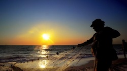 Silhouette of traditional fishermens pulling net fishing at ocean coast at sunset