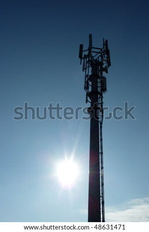 Silhouette of transmitter tower with sun flare in blue sky