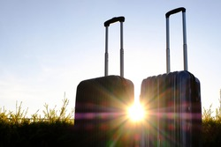 Silhouette of Travel suitcases, luggage or baggage on  Sunrise or Sunset background,The journey and  vacation concept or business travel, Finding solitude in the wilderness.