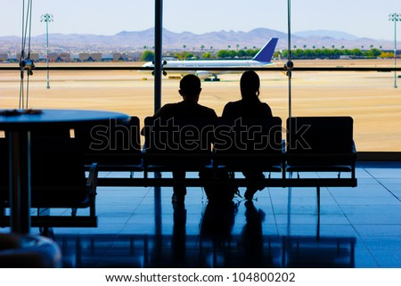 Silhouette of travelers in waiting area at airport with airplane visible on the runway outside