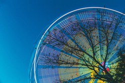 Silhouette Of Tree Branches Against Backdrop Of Bright Spinning Ferris Wheel At Spring Evening Or Night. Motion Blurred Effect Around Of Rotating Illuminated Attraction Feature In City Amusement Park.