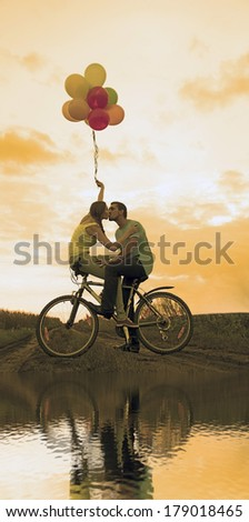Silhouette of two beautiful adult people looking each other Young couple sitting at one bicycle Girl holding baloons on sunset cloudy sky park background Copy space for inscription Reflection on water