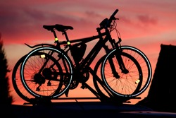 Silhouette of two bikes