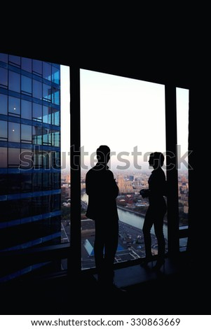 Silhouette of two confident colleagues having conversation while standing in corridor big company near window in evening time, young skilled workers discuss ideas after business meeting with partners