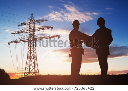 Silhouette Of Two Engineers Discussing Together With Electricity Pylon In Background #725063422