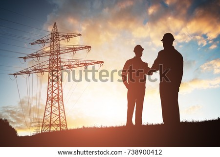 Silhouette Of Two Engineers Shaking Hands With Electricity Pylon Against Dramatic Sky