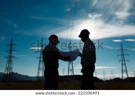silhouette of two engineers standing at electricity station, discussing plan stock photo