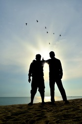 silhouette of two friends near the beach