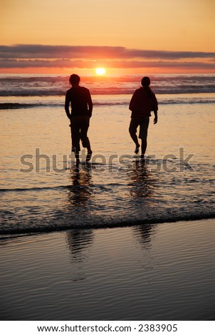 Silhouette of two girls wading in the ocean at sunset - stock photo