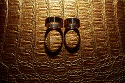 silhouette of two gold  wedding rings on a leather surface close up. wedding concept. wedding day. wedding background. bride and groom jewerly isolated.
