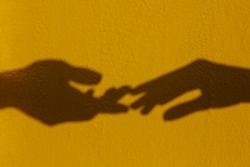Silhouette of two hands are drawn to each other on a yellow isolated background