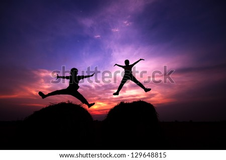 Silhouette of two happy children jumping at once during sunset
