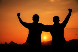 Silhouette of two man with success in sunset mountains.