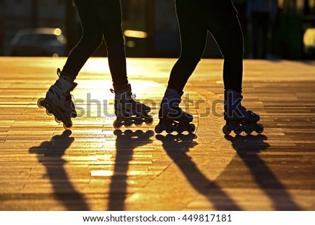silhouette of two pairs of legs on roller skates