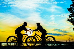 Silhouette of two people on romantic date looking each other. Young couple sitting at two bicycle Girl holding man's hand on sunset cloudy sky trees park background. Copy space for inscription
