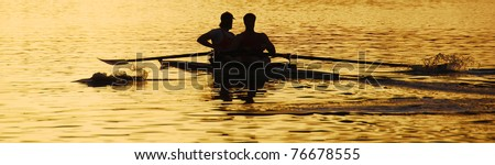 silhouette of two people rowing a boat  in the river with special aspect for banner usage