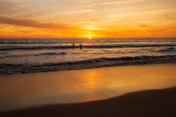 Silhouette of two people swimming to the Pacific ocean at sunset.