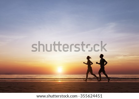 Silhouette of two sportive runners running on the beach at sunset, concept about healthy lifestyle and well-being