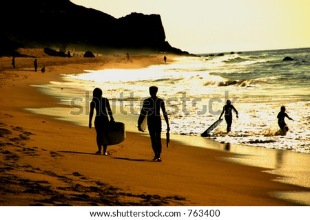 Silhouette of two surfers walking on beach, people playing in background.- soft focus