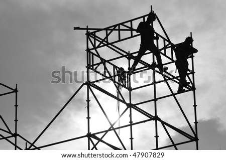 silhouette of two worker step on the falsework