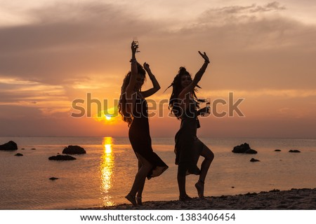 silhouette of two young beautiful girls having fun on the beach at sunset