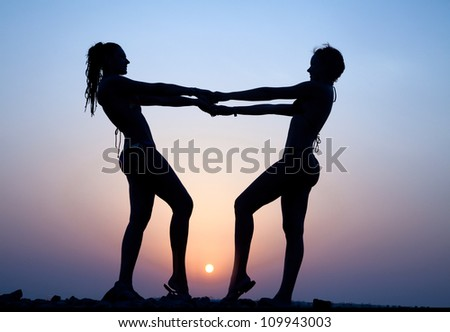 Silhouette of two young women against the evening sunset