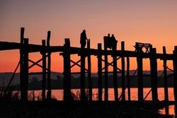 Silhouette of U Bein Bridge at sunrise. It is a crossing that spans Taungthaman Lake, Amarapura in Myanmar, former Burma. Oldest and longest teakwood bridge of the world.