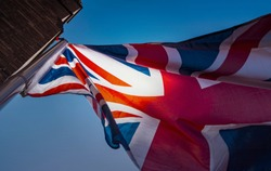 Silhouette of UK British Flag with blue Sky and Sun Waving Flag of the Great Britain