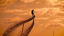 Silhouette of unrecognizable daredevil standing on flyboard and flying up in sky on background with orange clouds