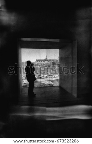 Silhouette of unrecognizable person in a window niche taking a photo, heavily textured in black and white tones with random light effects on floor and walls. #673523206