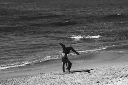 Silhouette of unrecognizable young woman practicing handstand at sea beach. Tel-Aviv, Israel. Black white photo. Fitness in nature background. Healthy lifestyle concept. Waves metaphor.