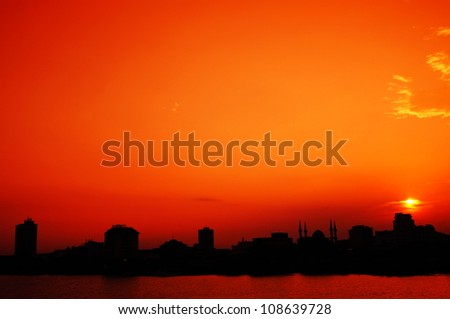 silhouette of urban skyline isolated on orange sunset view and reflection of river