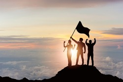 Silhouette of victory business team on mountain with sunset and sky background. Business teamwork success and leadership concept.