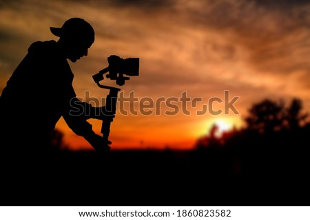 Silhouette of videographer is filming with cinema gimbal video dslr at sunset , professional video, videographer in events. Cinema lens on gimbal. Medium shot from right side. Film or cameraman school