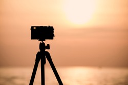 silhouette of vintage camera on tripod shooting beautiful calm sea with sun reflection on water at sunrise or sunset, image with copyspace