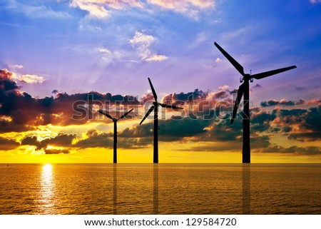 Silhouette of wind power stations over the sea at sunset.