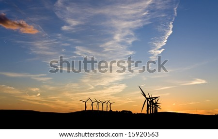 Silhouette of wind turbines against a sunset