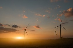 Silhouette of wind turbines. Beautiful view of wind generators in the mountain hill at sunset.