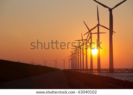 Silhouette of windmills with a sunset