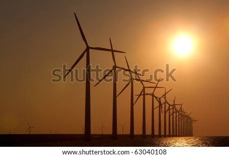 Silhouette of windmills with a sunset - stock photo