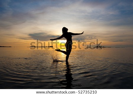 Silhouette of woman dancing in the shallow sea at sunrise