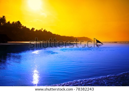 Silhouette of woman doing yoga Utthita Parsvakonasana triangle pose on the beach at the sunset in blue and orange colors