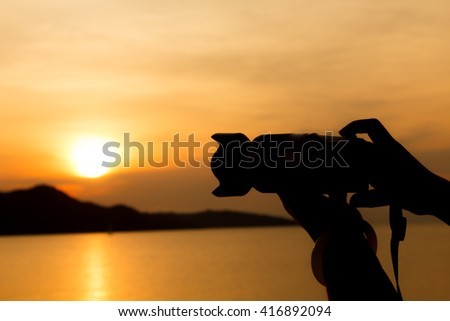 silhouette of woman hand using the digital camera take photho when sunrise #416892094
