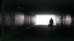Silhouette of woman in dark underpass. Danger of loneliness and insecurity in city