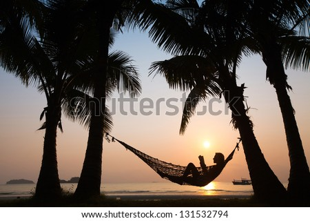 silhouette of woman in hammock at sunset on the beach